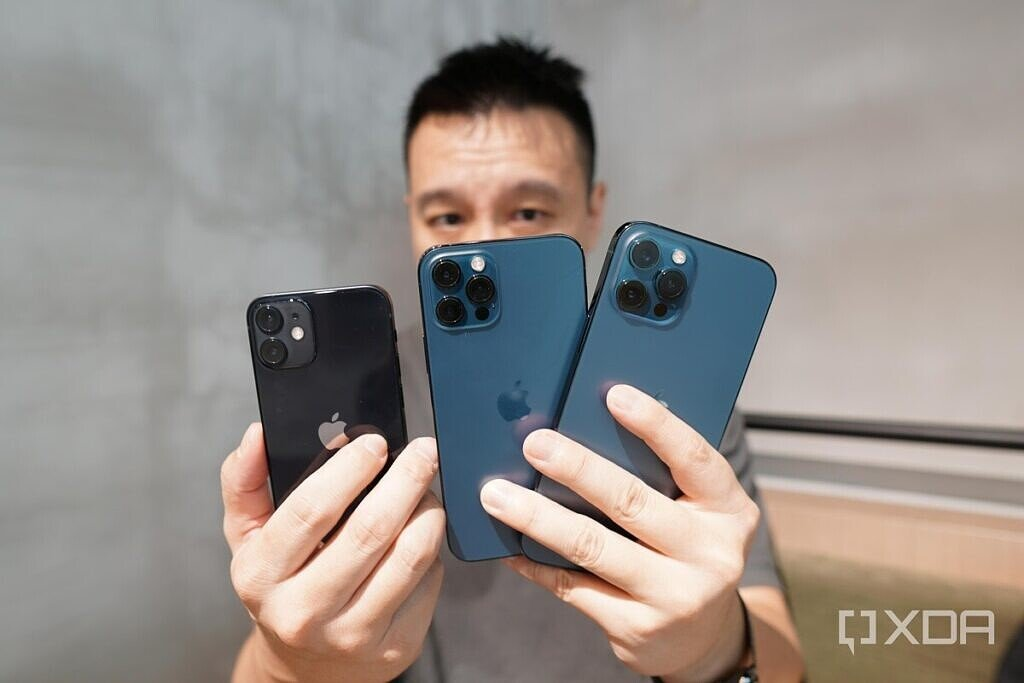 Holding the iPhone 12 Pro Max, iPhone 12 Pro and iPhone 12 Mini.